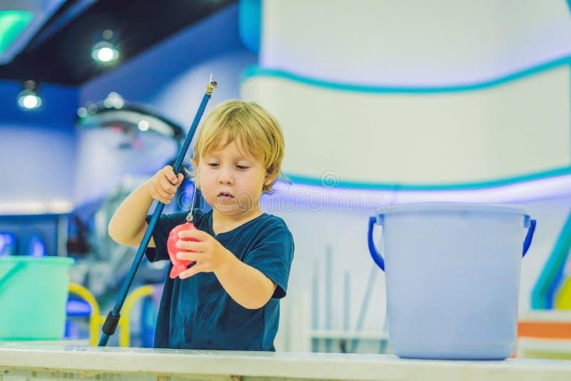 Leuke jongen in de speelkamer visserij De ontwikkeling van fijn motorconcept Het concept van het creativiteitspel stock fotografie