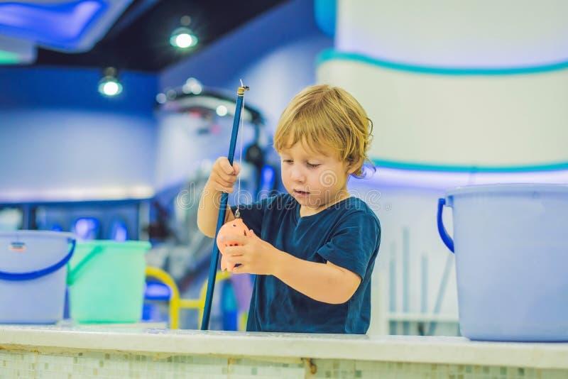 Leuke jongen in de speelkamer visserij De ontwikkeling van fijn motorconcept Het concept van het creativiteitspel stock afbeelding