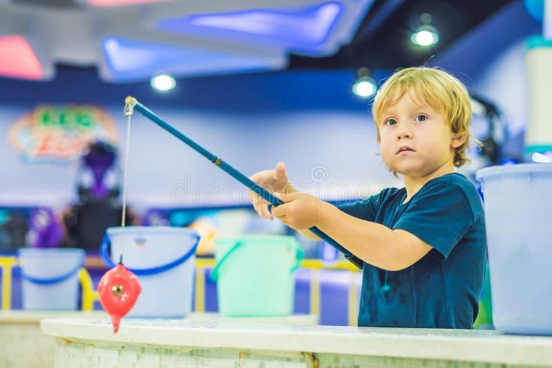 Leuke jongen in de speelkamer visserij De ontwikkeling van fijn motorconcept Het concept van het creativiteitspel stock foto