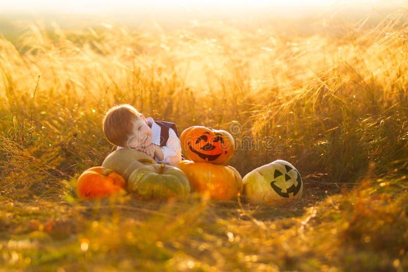 Leuke jongen die de herfst van tijd genieten Weinig jongen met pompoenen voor Halloween over zonsondergang of zonsopgangachtergro royalty-vrije stock afbeelding