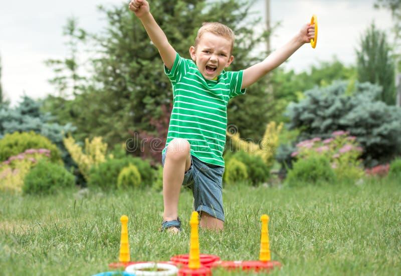 Leuke jongen die een spel spelen die ringen in openlucht in de zomerpark werpen De vreugde van overwinning stock afbeelding