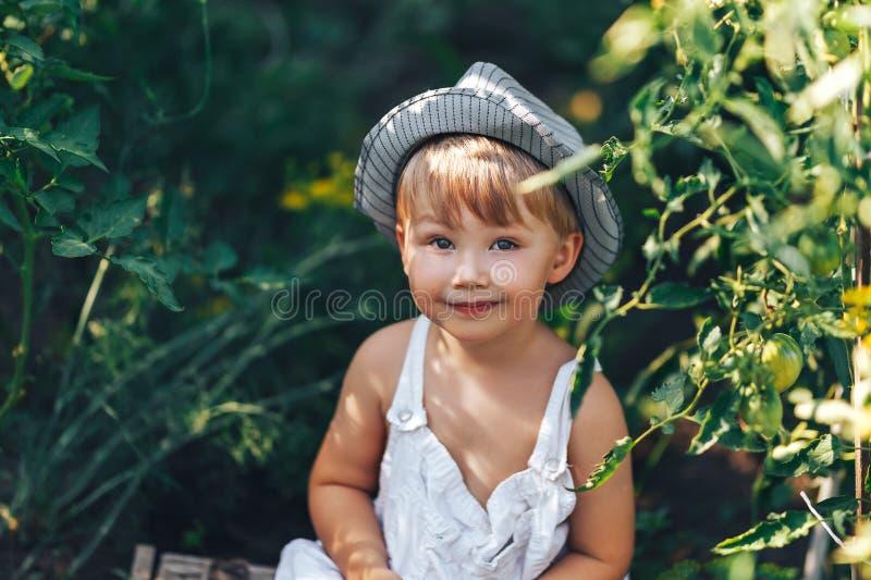 Leuke jongen die in hoed en vrijetijdskleding tomatenang rondhangen die camera, jong geitje het model stellen in tuin bekijken stock afbeelding