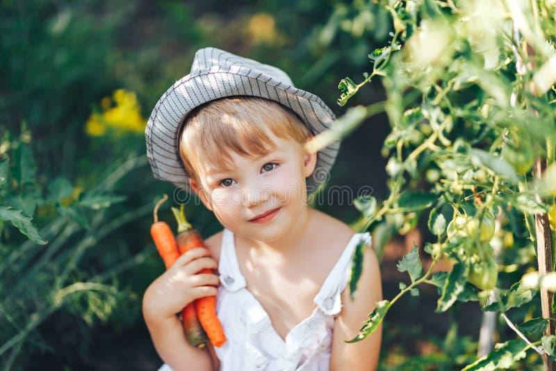 Leuke jongen die in hoed en vrijetijdskleding tomatenang rondhangen die camera, jong geitje het model stellen in tuin bekijken stock foto's