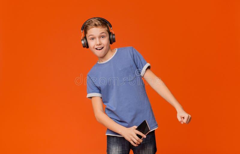 Leuke jongen die in hoofdtelefoons aan muziek op telefoon luisteren royalty-vrije stock afbeelding