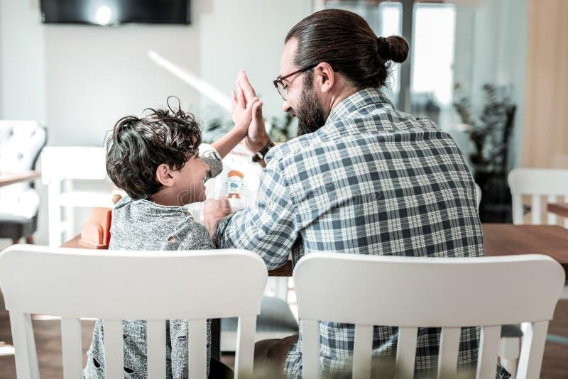 Leuke jongen die hoogte vijf zijn vader na samen het lezen van boek geven royalty-vrije stock afbeelding