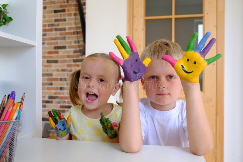 Leuke jongen die met geschilderde handen met zijn kleine zuster thuis spelen royalty-vrije stock afbeeldingen