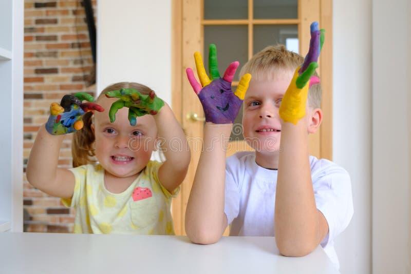 Leuke jongen die met geschilderde handen met zijn kleine zuster thuis spelen stock afbeelding