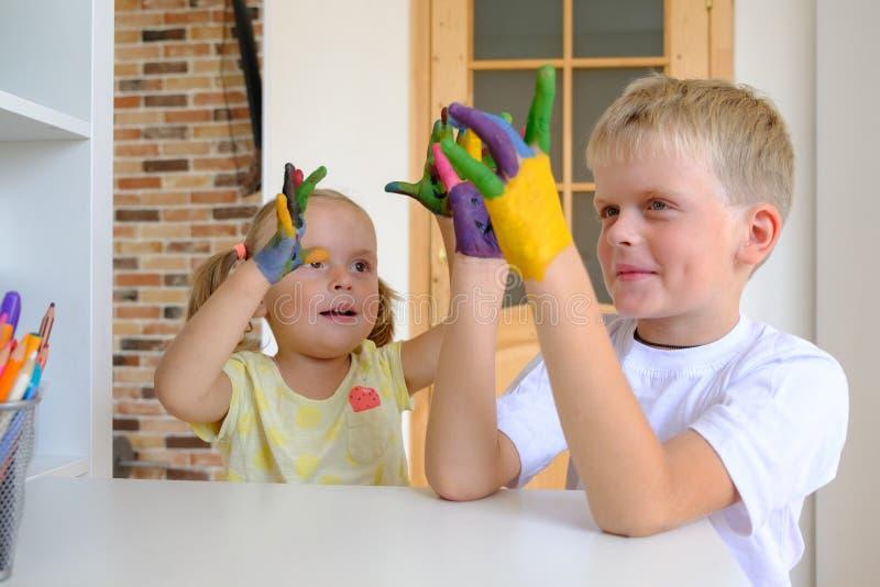Leuke jongen die met geschilderde handen met zijn kleine zuster thuis spelen royalty-vrije stock foto's