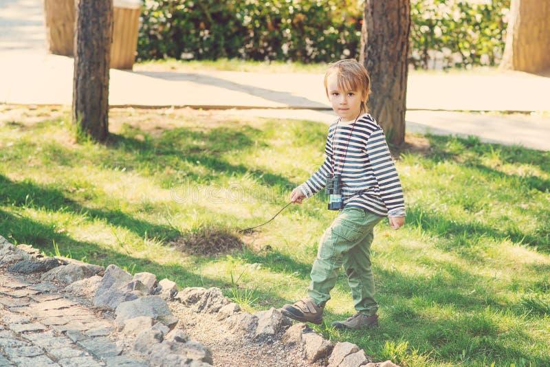 Leuke jongen die met houten stok in zijn hand in openlucht spelen Onbezorgde kinderjaren royalty-vrije stock afbeeldingen