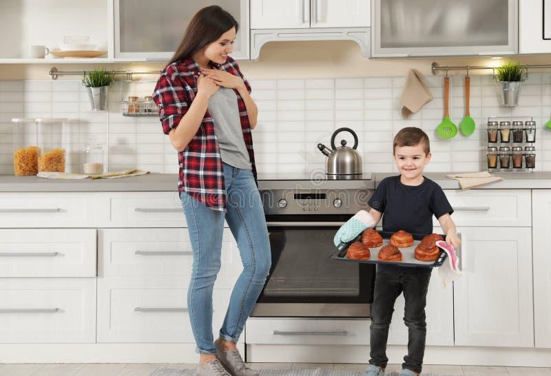 Leuke jongen die moeder behandelen met oven gebakken broodjes royalty-vrije stock afbeeldingen