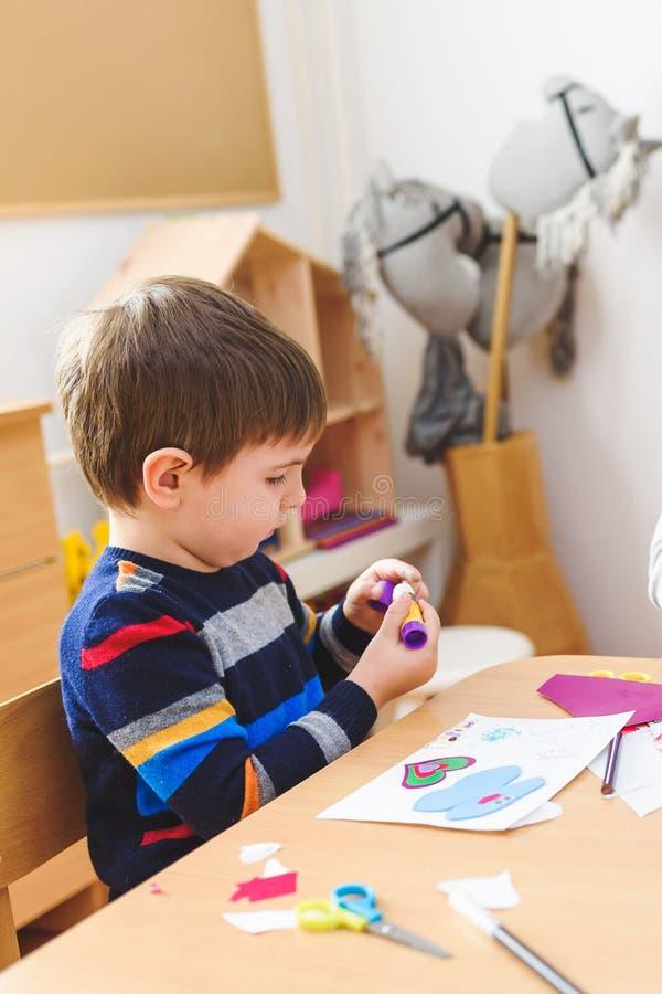 Leuke jongen die op de klasse van de kleuterschoolkunst kleurrijk document lijmen stock afbeelding