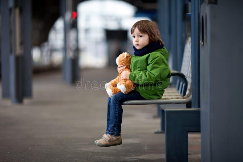 Leuke jongen, die op een bank met teddybeer zitten, die een trein bekijken royalty-vrije stock afbeelding