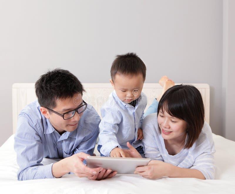 Leuke jongen die tabletPC met gelukkige familie met behulp van stock fotografie