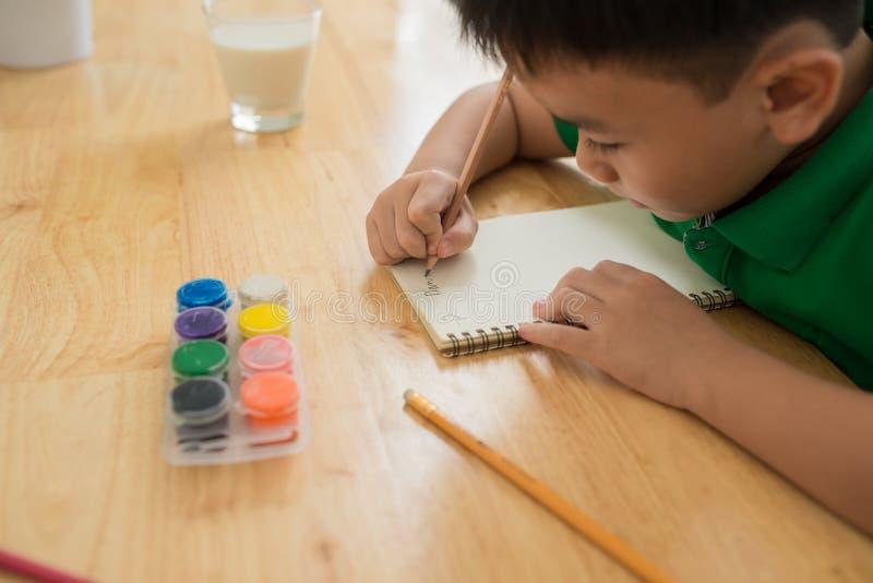 Leuke jongen die thuiswerk, het kleuren van pagina's, het schrijven en het schilderen doen De kinderen schilderen De jonge geitje stock afbeeldingen