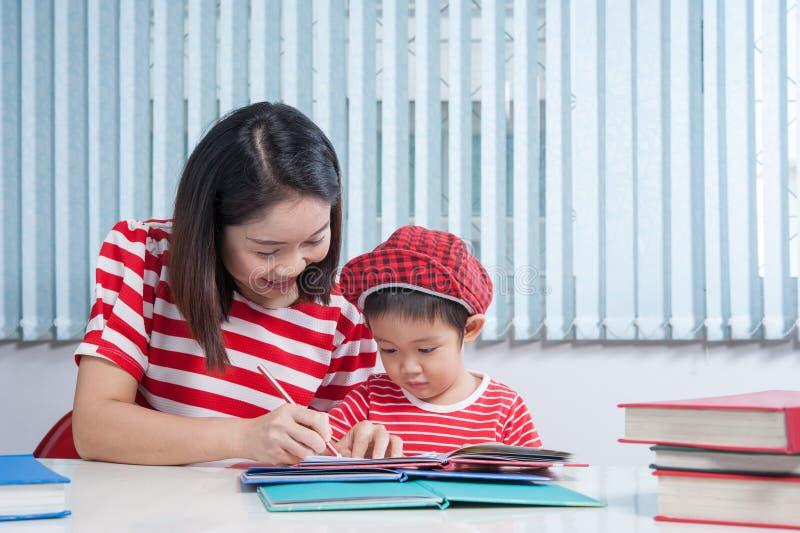 Leuke jongen die zijn schoolthuiswerk met zijn moeder doen, thuis, hij stock afbeelding