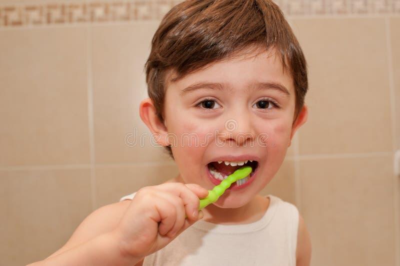 Leuke jongen die zijn tanden wassen stock foto's