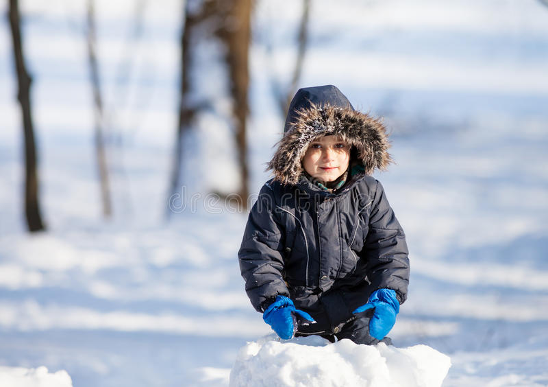 Het leuke jongen spelen met sneeuw stock afbeeldingen
