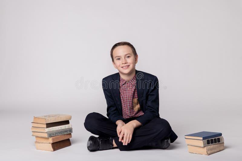 Leuke jongen in een kostuum zitting en het glimlachen op een witte achtergrond Stapel van boeken stock afbeelding