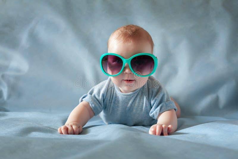 Leuke jongen in groene zonnebril die op een het blauwe achtergrond en glimlachen liggen royalty-vrije stock afbeeldingen