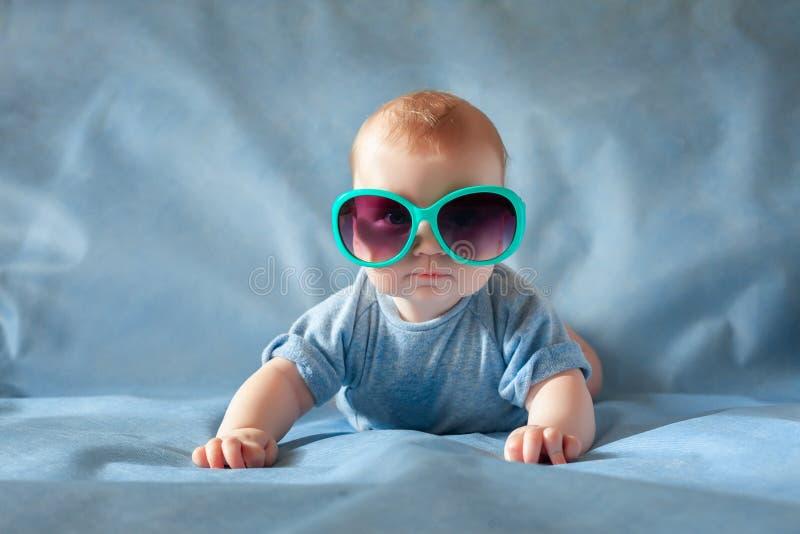 Leuke jongen in groene zonnebril die op een het blauwe achtergrond en glimlachen liggen royalty-vrije stock foto