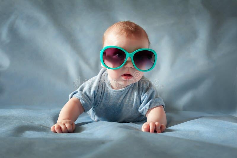 Leuke jongen in groene zonnebril die op een het blauwe achtergrond en glimlachen liggen stock afbeeldingen