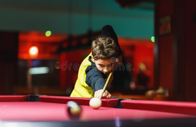 Leuke jongen in het gele biljart van t-shirtspelen of pool in club Het jonge Jonge geitje leert om snooker te spelen Jongen met b stock foto