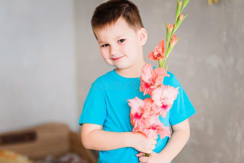 Leuke jongen met gladiolen stock afbeelding