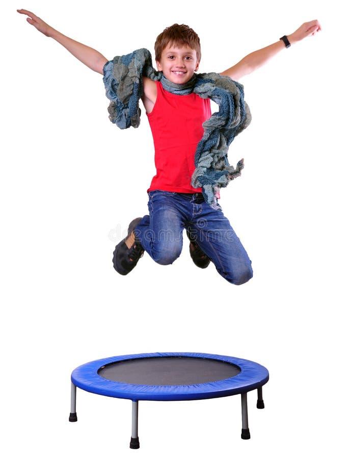 Leuke jongen met sjaal die en op een trampoline uitoefenen springen royalty-vrije stock afbeelding