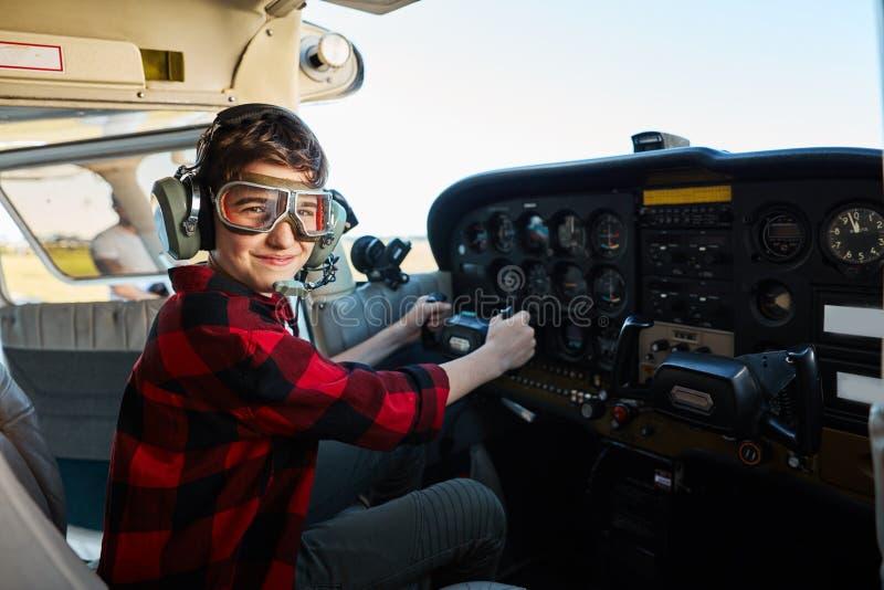 Leuke jongen in van de vliegeniersglazen en hoofdtelefoon zitting in vliegtuigcockpit royalty-vrije stock afbeeldingen