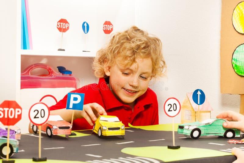 Leuke jongens speelbestuurder met stuk speelgoed document auto's stock foto's