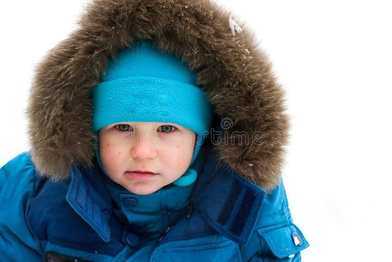 Leuke jongenszitting in sneeuw openlucht stock foto
