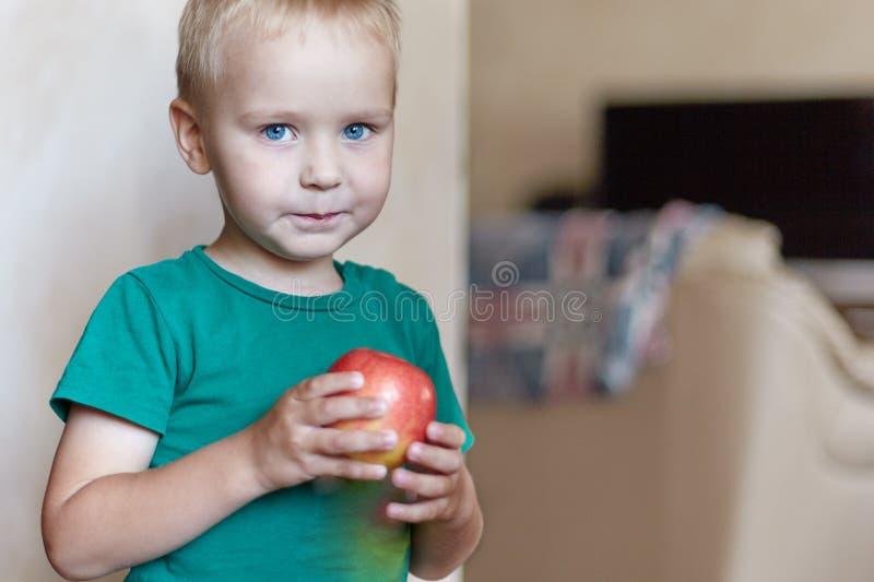 Leuke Kaukasisch weinig jongen met blauw ogen en blondehaar in groene t-kort eet rode appel, houdend het op de handen stock fotografie