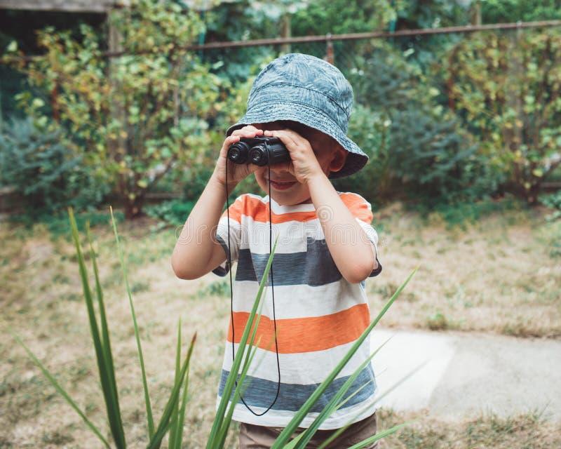 leuke Kaukasische jongen in gestripte t-shirt en hoed die door verrekijkers kijken stock foto's