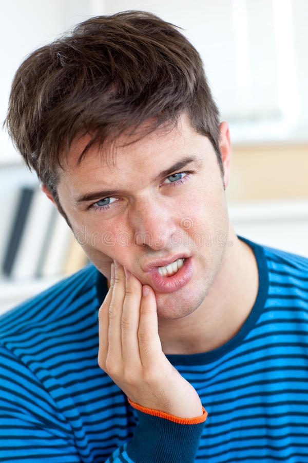 Leuke Kaukasische mens die een tandpijn heeft thuis stock fotografie