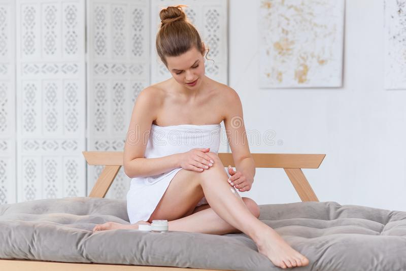 Leuke Kaukasische vrouw die in witte handdoek room op haar huid toepassen vóór kuuroordprocedure aangaande de witte salonachtergr royalty-vrije stock afbeelding