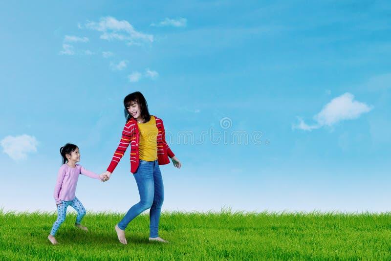 Leuke kind en moeder die op weide lopen stock foto