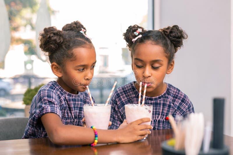 Leuke kind-hearted zusters die hun melkcocktails met elkaar delen royalty-vrije stock foto's