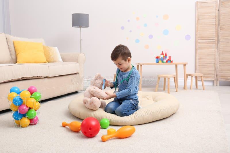 Leuke kind speelarts met gevuld stuk speelgoed op vloer royalty-vrije stock fotografie