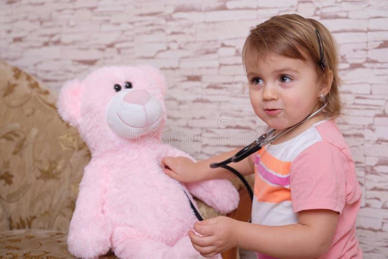 Leuke kind speelarts of verpleegster met pluchespeelgoed thuis stock foto's
