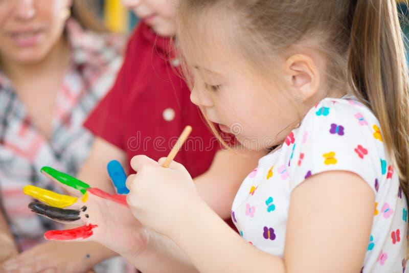 Leuke kinderen die bij kleuterschool schilderen stock fotografie