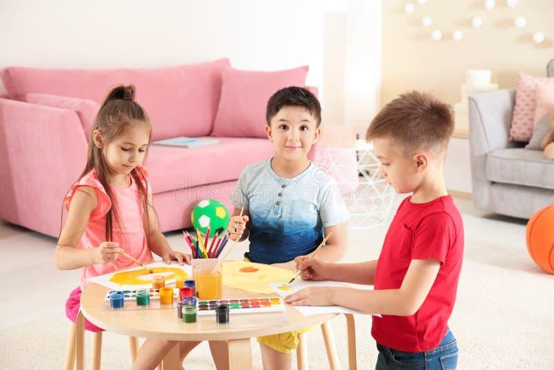 Leuke kinderen die bij lijst in het spelen ruimte schilderen royalty-vrije stock afbeelding