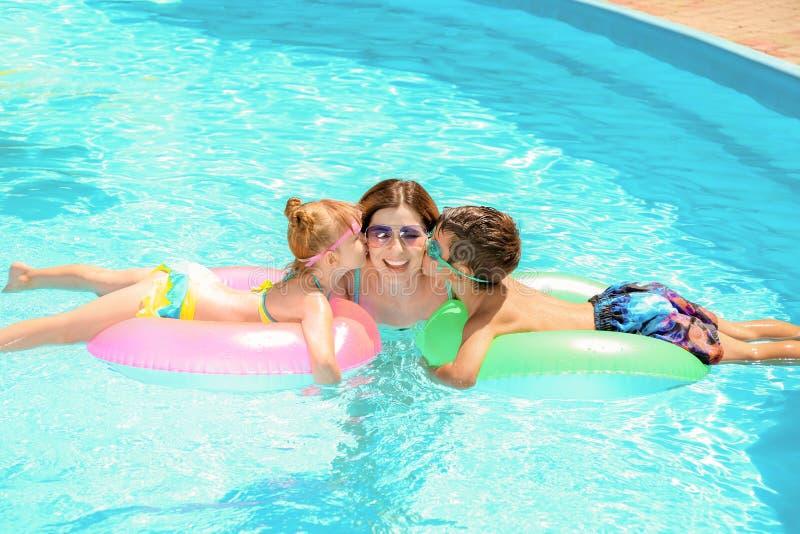 Leuke kinderen die hun moeder in zwembad kussen royalty-vrije stock foto's