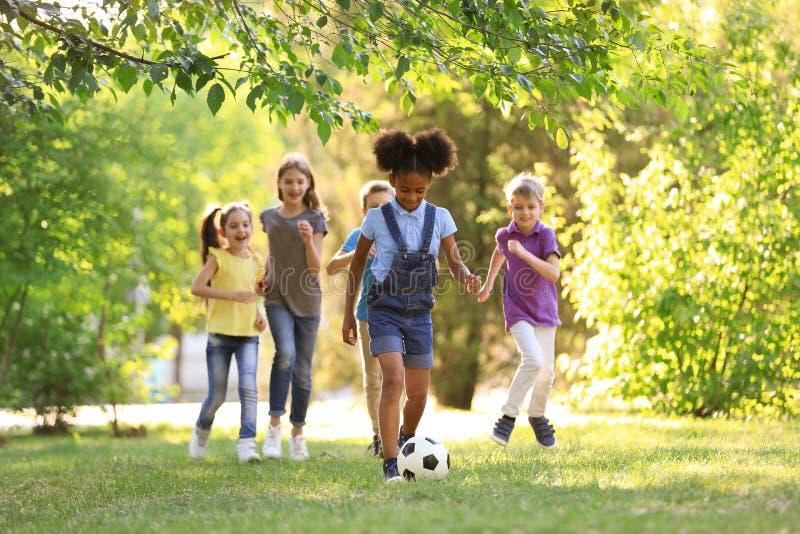 Leuke kinderen die met bal in openlucht op zonnige dag spelen royalty-vrije stock afbeeldingen