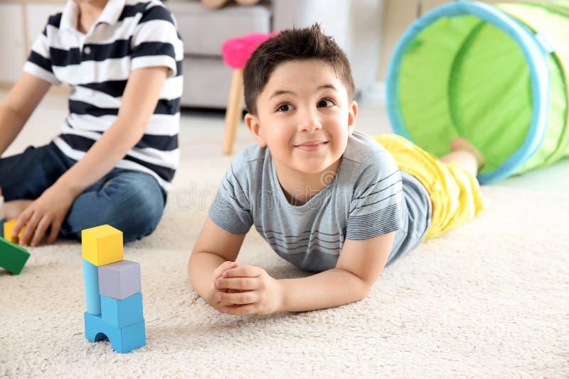 Leuke kinderen die met bouwstenen op vloer spelen, binnen royalty-vrije stock afbeelding