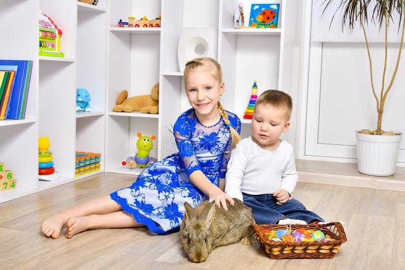 Leuke kinderen die met een konijn voor Pasen spelen stock foto