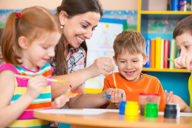 Leuke kinderen die met leraar bij peuterklasse trekken stock afbeeldingen