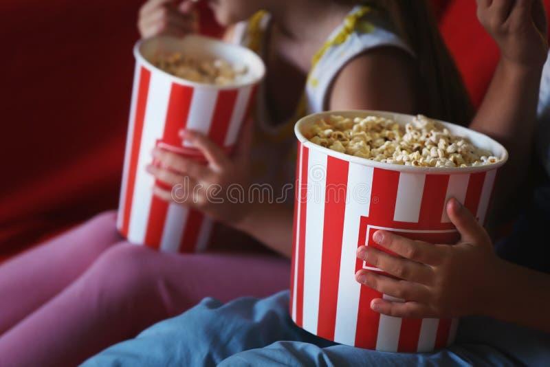 Leuke kinderen die popcorn eten terwijl het letten van op TV in avond royalty-vrije stock fotografie