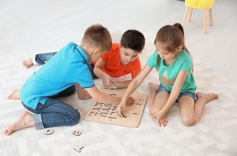 Leuke kinderen die samen op vloer spelen, binnen stock foto