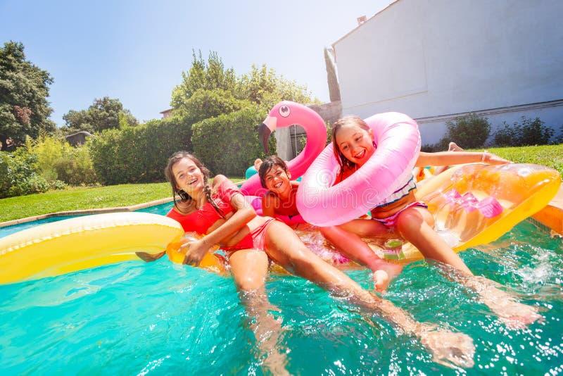 Leuke kinderen die van zomer in openluchtpool genieten stock afbeelding
