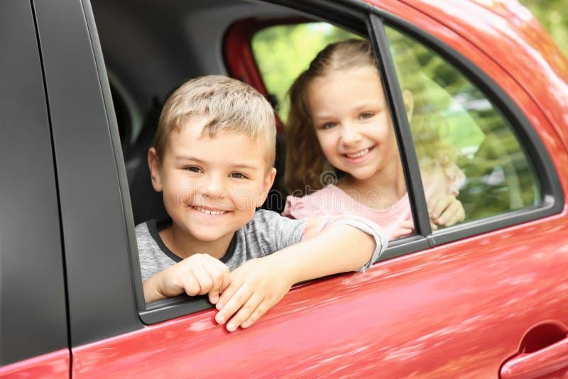 Leuke kinderen op achterbank van auto stock afbeelding